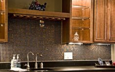 This kitchen backsplash opts for a darker tone. Photo by 2 Gays & A Design.