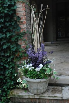 Simple fall pots-charming. Bleached stick stacks, white pansies, and variegated ivy go well together. The addition of a bunch of lavender preserved eucalyptus adds an element of color that is welcome, and visually striking.