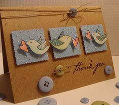 kraft card with blue inchies topped by birds with hearts...twine and buttons too...