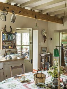 In the kitchen, a horseshoe sits above a rack of tin plates and, on the Corsican tablecloth, gooseberries and wildflowers from the garden, an olive-picking basket from Greece and late 18th-century silver-plated candlesticks.