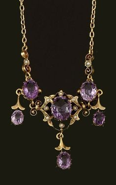 An amethyst and seed pearl necklace  Composed of three graduated pendant drops of foliate design, set with oval-cut amethysts, the central pendant bordered by seed pearls, to a fine belcher-link back chain, length 38cm.