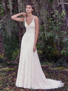 Maggie Sottero - JORIE, Dreamy and alluring, this A-line wedding dress features a Vogue satin slip and an intricately embroidered overlay with lace. A plunging V-back and beaded belt completes this romantic gown. Finished with covered buttons over zipper closure.