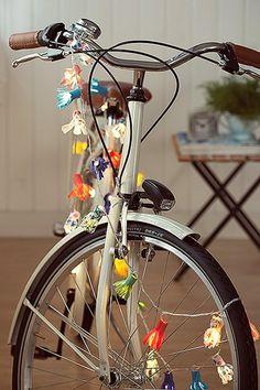 """Feitas de feltro, com uma """"franja"""" recortada, as florzinhas envolvem as lâmpadas e transformam até a bike em item de decoração."""