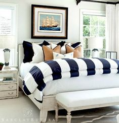 folded striped duvet at end of bed | white sheets / coverlet