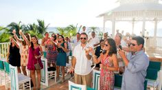 Wedding guests toast the happy couple at the end of the beach ceremony | Palace Resorts #destinationwedding