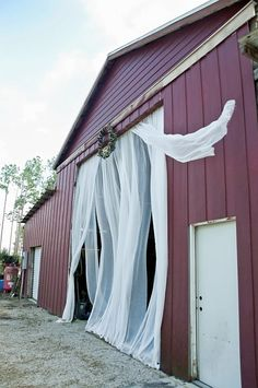 Fall country wedding. Cheese cloth hanging from barn doors.   Cleopatra Photography