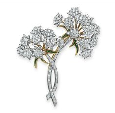 A DIAMOND AND TSAVORITE GARNET BROOCH, BY TIFFANY & CO. Designed as two circular-cut diamond Queen Anne's Lace flower blossoms