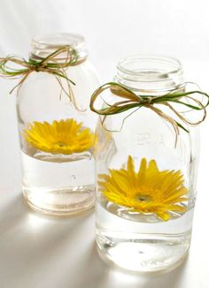 Sunny Display ~ Floating a single blossom in a jar with a little water makes a charming display. A bow of raffia tops it with flourish.