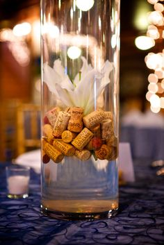 inside tall centerpieces: wine corks and lily made by flora d'amore