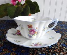 This is a prettyShelley China, England bone china cup and saucer in a rarely seendesign. pattern name: Universal Rose And Bluebell pattern number: 13796 Strat