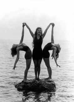 Three of film-maker Mack Sennett's famous bathing beauties  pose as nymphs on a rock off the coast of the USA, in 1922.