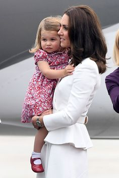 Princess Charlotte of Cambridge adorable in a floral dress teamed with red shoes and white socks, while her mother Catherine, Duchess of Cambridge kept it simple in a white peplum coat by her go-to designer Alexander McQueen as they arrives at Warsaw airport on day one during an official visit to Poland and Germany on July 17, 2017