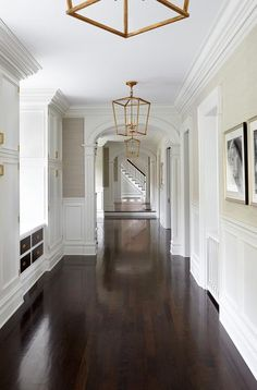 Arched doorways add the perfect touch to this stunning long hallway boasting wainscoting on the lower walls and mushroom colored grasscloth and crown moulding on the upper walls accented by the rich color of dark hardwood floors illuminated by a series of Darlana 4 Light Foyer Lanterns by Visual Comfort.