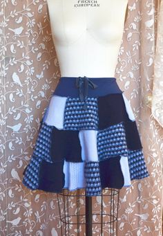 One of a kind womens a line sweater skirt in shades of blue and houndstooth pattern with blue exposed serger seams. Eco-friendly, comfortable and flattering skirt. Made from super soft, washed, repurposed lambswool sweaters. One size fits many women, in S/M range. It measures 17.5 long, and fits waists 26-34 and hips up to 44. It has a comfy blue organic cotton/bamboo/spandex jersey knit waistband with an elastic drawstring for further adjusting the fit. Its super twirly, sassy and fun. Hand…