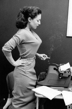 Brazilian writer Clarice Lispector peering down at her typewriter while smoking a cigarette, ca. 1950s