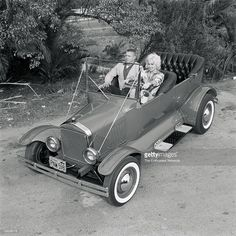 """Mamie Van Doren & Norm """"Woo Woo"""" Grabowski with his bright red 1925 T Tub. Norm looks just a bit tense as Mamie Van Doren takes control of his latest hot rod. Norm and car have featured roles in the 1960 movie """"Sex Kittens Go To College"""". Mamie Van Doren, Classic Hot Rod, Old Classic Cars, Carros Hot Rod, Hot Rods, T Bucket, Retro Futuristic, Us Cars, Once In A Lifetime"""
