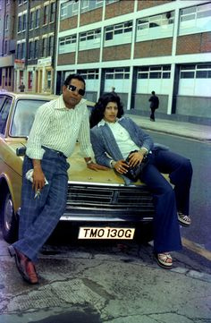 COUPLE POSING WITH THEIR FORD CAR. EAST LONDON UK 1970'S