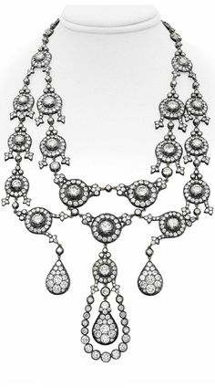 A DIAMOND NECKLACE. Designed as a necklace suspending a two-tiered graduated series of old-cut diamond swags, each old-cut diamond within a diamond surround, spaced by collet-set diamond links, the front suspending three drop-shaped old-cut diamond clusters, 21 1/4 ins., mounted in silver-topped gold