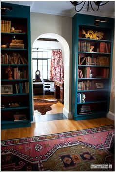 A library-like nook connects the home office to the kitchen. The shelves are filled with antique books and treasures from her family's New Hampshire farmhouse.    BOOKCASE COLORS:  Paint: Dark Teal 2053-20 and Dinner Party AF-300, both by Benjamin Moore  Rug: Terra Kilim, Pottery Barn