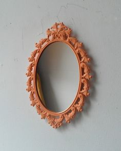 Oval Wall Mirror in Vintage Brass Feather Frame - Light Peach. $25.00, via Etsy.