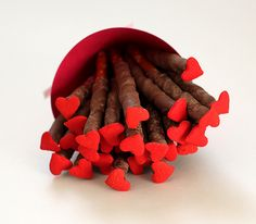 Cute Valentines treat idea! Chocolate covered pretzels with candy heart stuck on the end.