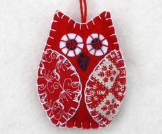 Three owl ornaments in red and white, handmade from felt and cotton prints with hand embroidered details. Each owl is 8cm high and has a cotton loop for hanging. The listing is for a set of 3 owls. I'
