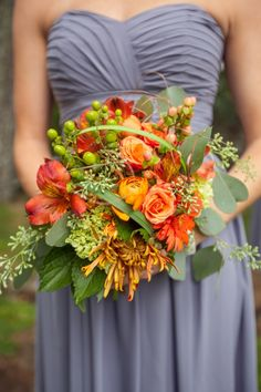 Orange roses, ranunculus, alstromeria, gerbera daisies and spider mums with green mini hydrangea, green hypericum berries, seeded eucalyptus and bear grass.