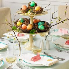 Brightly colored Easter eggs in green, pink, orange, green on a yellow 2 tiered cake stand.  Tablescape table setting for Easter brunch or dinner.  Shabby Cottage