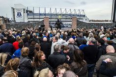 People gather at the family memorial wall and dixie dean statue.