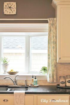 Added linen cafe curtain with pom-pom trim to soften kitchen window.