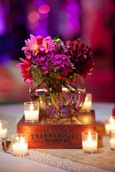 Centrepiece idea: Fishbowl with bright blooms on a vinatage box with candles. Simple yet effective
