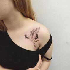 Illustrative tattoo of a crane on chest/shoulder. Tattoo artist: Hongdam