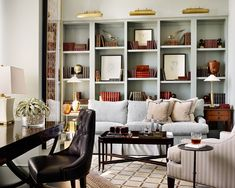 Library designed by Lauren DeLoach with built in bookshelves and blue sofa