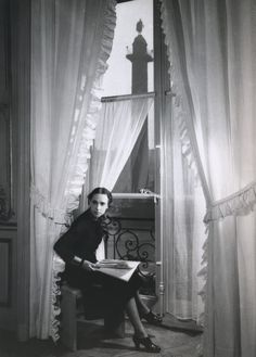 """Haute couturière Elsa Schiaparelli in a window of her showroom at 21 Place Vendôme in Paris. Image by François Kollar from """"Good Housekeeping, June 1938"""
