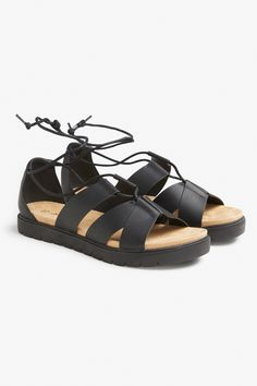 Form a summer outfit dreamteam with this rockin' summer sandal. With black faux leather straps and ballerina style lacing, these look crazy awesome with culottes or whatever else you're feeling! Black Sandals, Gladiator Sandals, Leather Sandals, Magic Shoes, Wooden Clogs, Dream Shoes, Black Faux Leather, Monki, Winter Boots