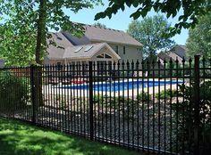 Black wrought iron fence around pool.