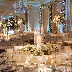 ivory and white wedding reception decor with white florals in glass vessels
