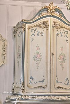 French armoire hand painted with sprays of flowers.