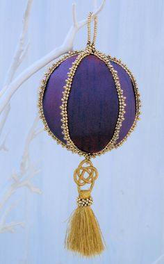 A 6 sided shape that forms a ball tree decoration in purple silk, with gold beads and a golden tassel