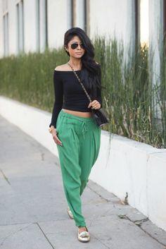 mujer pantalon verde con blusa negra y lentes negros