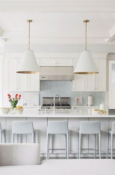 Light blue herringbone backsplash in a white kitchen with a couple of our favorite chandeliers!