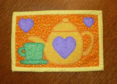 """PDF Pattern to make this tea themed mug rug or teapot mini quilt. Made with these teapot, cups, and heart appliques. Measures 6 1/2"""" x 10""""  You can use them for setting your mug on with a snack, or my favorite way, leaning them against the wall in my hutch. You can even stitch rings to the back and hang on your wall.  These are the funnest of things to make! If you choose the machine applique, you can whip these up in no time. They make great gifts when given with a cute mug. They are so…"""
