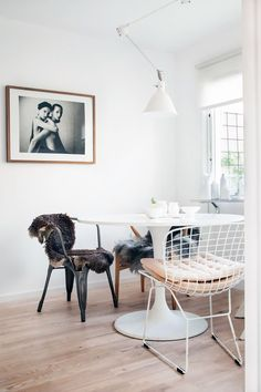 Minimalist dining space with a marble table, wire chairs, and black and white photography