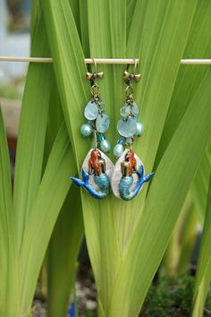 My earrings for Sunday Earring Challenge Board for 05.03.15. These mermaids were painted with Lumiere paints, then glued to these lovely shell pieces, hung on B'Sue Brass Ox chain and Bow earrings with turquoise beads and shells.