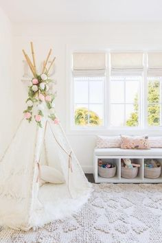 Alyssa Rosenheck - Amanda Barnes Interior Design - Ethereal girl's nursery features a white boho teepee placed atop a round sheepskin rug tucked into the corner of the room placed next to a white storage bench filled with gray woven baskets and lined with pink trellis pillows placed under a window dressed in light gray roman shades accented with tassel trim.