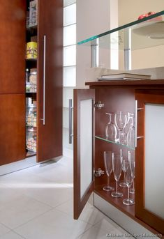 #Kitchen Idea of the Day: Natural warmth: Modern wood kitchens in medium tones. The back of this kitchen island has shallow glass cabinets for storing china. Note also the glass bar top supported by aluminum bars and the pull-out pantry. Beautiful!