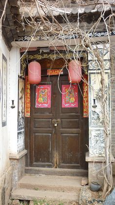 A compound with doors brightly decorated with Chinese New Year door gods, couplets and lanterns in Shaxi.