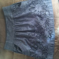 Stooshy gray skirt! Gray denim look with flowers around he bottom of the skirt. Pockets in the front of the skirt. Size M. Has elastic in the waist. Stooshy Skirts