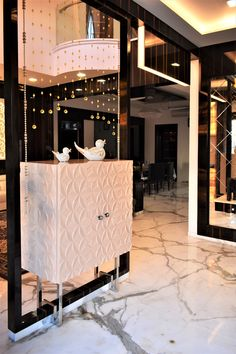 A semi partition is created with luxury and classy storage unit on the left side which houses a flower motif CNC pattern lending warmth by A.J Architects.