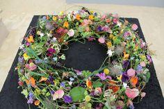 Een bloemstuk met vrolijke en lichte kleuren | Vind meer inspiratie over bloemen voor het afscheid en de uitvaart op http://www.rememberme.nl/rouwbloemen-rouwdecoratie/